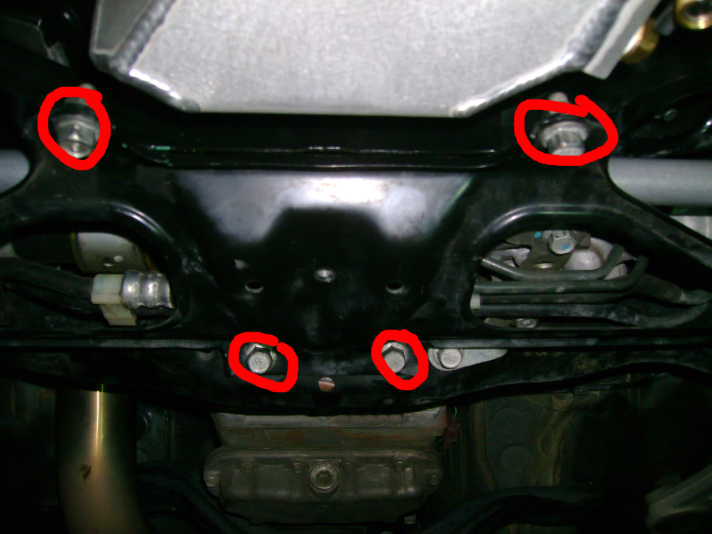 Subaru STi: Remove the subframe lower brace as seen here. Ten total bolts, all 14mm (two have 14mm nuts) and you may need your impact/breaker bar. There are four center bolts as circled below (note that the forward two have a nut instead of threads into the subframe).
